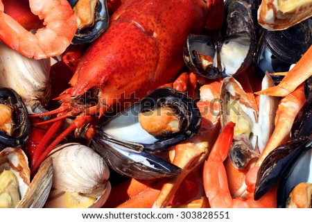 Shellfish plate of crustacean seafood as fresh lobster steamed clams mussels shrimp and crab as an ocean gourmet dinner background.