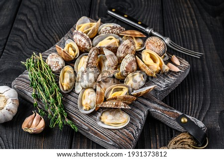 Shells Clams vongole on a wooden cutting board. Black wooden background. Top view. Сток-фото ©