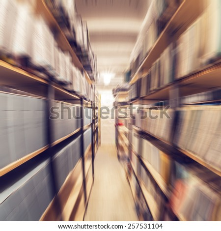 Shelves full of paper documents stored in an old archive. Radial zoom effect defocusing filter applied, with vintage instagram look.