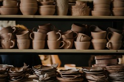 Shelves with ceramic dishware in pottery workshop