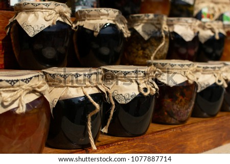 Shelves with composed handmade jam conserved in glass jars and decorated with strings. #1077887714
