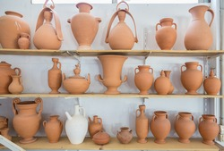 Shelves with different brown clay  jars and pots made by greek artists