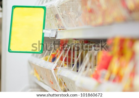 Shelves with food and info label in supermarket