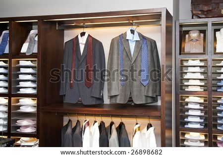Shelves with men shirts and suits in boutique