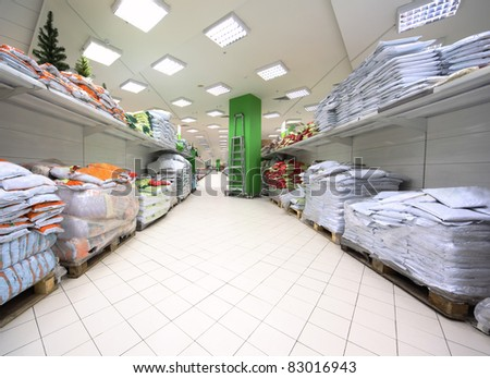 Shelves with variety of fertilizer and material for gardening inside large supermarket