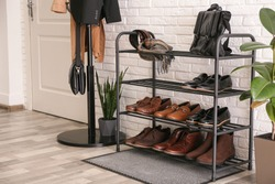 Shelving rack with stylish shoes and accessories near white brick wall indoors