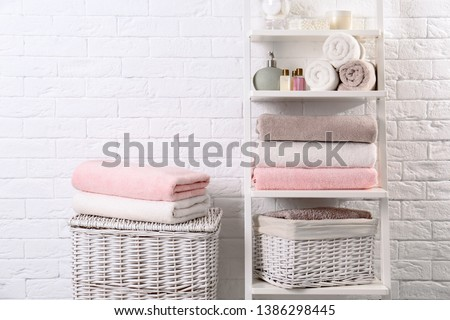 Shelving unit and baskets with clean towels and toiletries near brick wall Foto stock ©