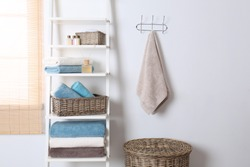 Shelving unit and rack with clean towels and toiletries near white wall