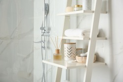 Shelving unit with different items in bathroom interior