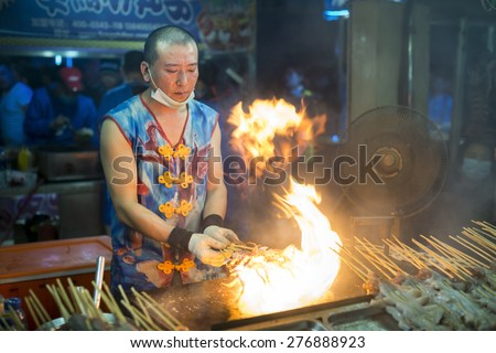 Shenyang, China - May 10, 2015: Chinese chef making Fire Iron Squid. Located in Xingshun International Tourist Night Market, Shenyang City, Liaoning province, China.