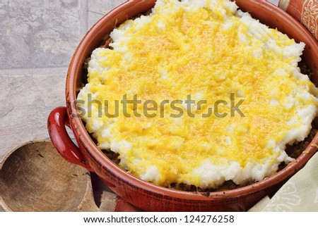 Shepard's Pie in a rustic casserole dish with wooden spoon.
