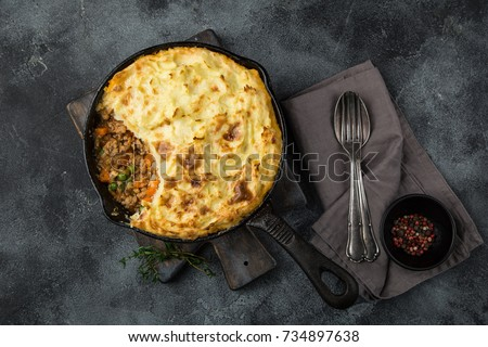 shepherd's pie. Minced meat, mashed potatoes and vegetables casserole in cast iron pan. Top view #734897638