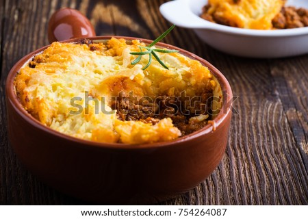 Shepherd's pie, traditional British dish with  minced meat and mashed potato on rustic wooden table #754264087