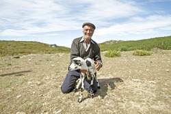 Shepherd with one of his goats in the countryside from Portugal