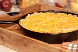 Shephers Pie baked in a cast iron skillet and placed on a wood tray with an apple and napkins