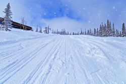Sheregesh ski resort in Russia, located in Mountain Shoriya, Siberia. Winter landscape blue colored, trees in snow and ski slope. View on Mount Utua.