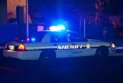 Sheriff cruiser car with his lights on at night on a call to protect the peace
