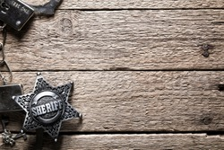 Sheriff star and handcuffs on wooden table closeup. Law concept background