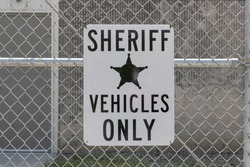 Sheriff Vehicles Only sign with five point badge. Only sheriff vehicles are allowed to park in the designated area.