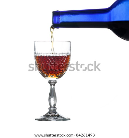Sherry, port or whisky being poured from blue wine bottle into an elegant cut glass and isolated against white