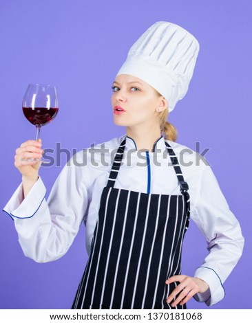 Shes a classy sommelier. Pretty woman holding glass of red wine. Wine professional at work. Adorable wine expert. Wine steward or waiter degustating alcoholic drink. #1370181068