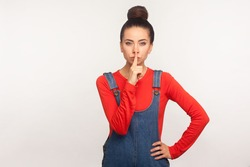 Shh, don't talk! Portrait of serious bossy girl with hair bun in denim overalls shushing, asking for silence or secrecy with finger on lips, be quiet. indoor studio shot isolated on white background