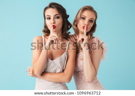 Shh! Image of two gorgeous women 20s wearing dresses and party makeup putting fingers on lips to keep secret isolated over blue background