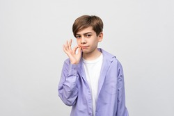 Shh its secret. Portrait of serious boy 12-14 years old showing zip gesture as if shutting mouth on key, promises to keep secret, wearing casual clothes, gray background, isolated