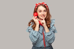 Shh, keep quiet! Pretty pinup girl holding phone handset looking at camera, asking for silence secrecy with finger on lips, confidential talk on telephone. studio shot isolated gray background,