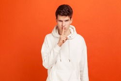 Shh sign. Concerned man holding finger near lips and showing silence sign. Keeping secrets, deceit. Indoor studio shot isolated on orange background
