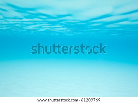 Shifting sand and moving water under the waves provides a blue abstract background