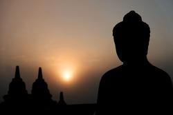 Shilouette Budha statue from Borobudur Temple with sunrise
