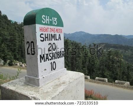 SHIMLA, INDIA, MAY-22-2014 : Milestone along way to Shimla with green forest beside road #723133510