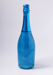 Shimmer edible glitter sparkling blue champagne in bottle on white background. Vertical format