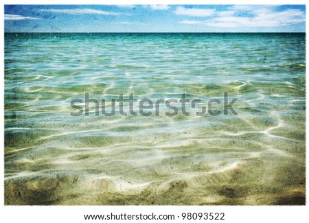 Shimmering aquamarine sea, with blue sky.  Grunge effects.