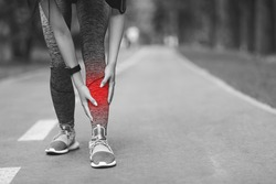 Shin Splints Injury. Female Athlete Massaging Injured Leg, Suffering From Trauma During Jogging In Park, Black And White Image With Red Sore Spot