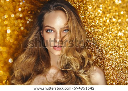 Shine make up of beauty young model. Star shine background. Blonde curly hair. Cosmetics.