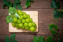 Shine Muscat Grape fruit on the brown wooden table, Green grape with leaves on a wooden background,