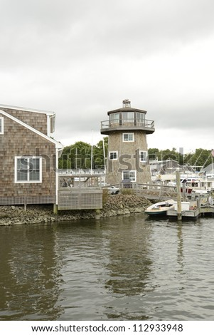 shingle style building and small lighthouse by the water in Essex Connecticut