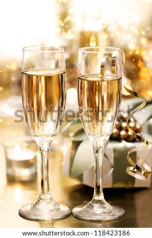 Shining champagne glasses with candles and gifts