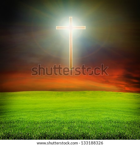 shining cross  over dark red sky and green field with grass - religion concept