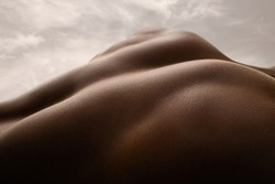 Shining. Detailed texture of human skin. Close up of young african-american male body surface like landscape with the sky on background. Skincare, bodycare, healthcare, inspiration, fantasy artwork.