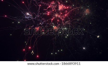 shining fireworks with bokeh lights in the night sky. glowing fireworks show. New year's eve fireworks celebration. multico lored fireworks in night sky. beautiful colored night explosions in black