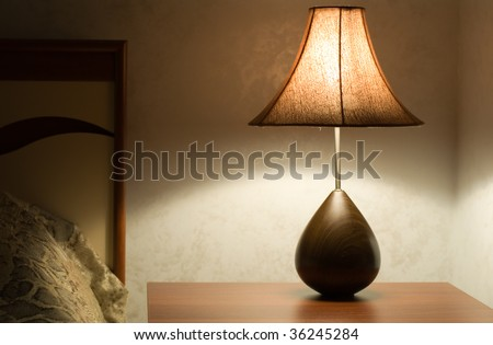 shining lamp on the table near bed