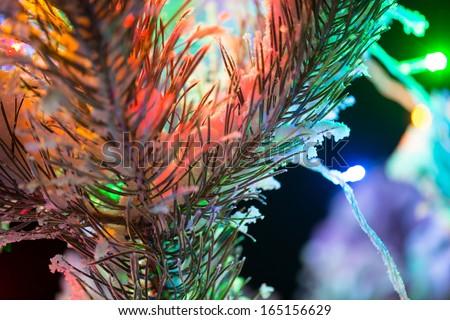 Shining lights of a natural Christmas tree covered snow. New years night black outdoor background. Close Up macro shoot.
