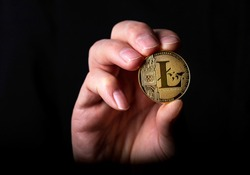 Shining litecoin golden LTC coin in male hand over black background.