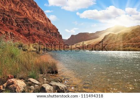 Shining rays of the sun reflected in the cold water of the Colorado River. The steep mountains of red sandstone.