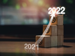 Shining rise up arrow on wooden blocks chart steps with percentage icons from year 2021 to 2022 on wooden desk, business growth process, and economic improvement concept.