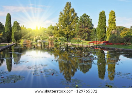 Shining sharp rays of the sun reflected in the smooth blue water of the pond