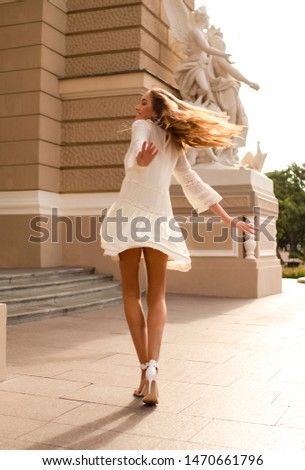 Shining young lady dancing outdoor on the street in the light white dress. Long blonde hair waving, wearing high heel shoes. Happy and funny girl with a sexy slim body and bronze skin. Summer vacation #1470661796